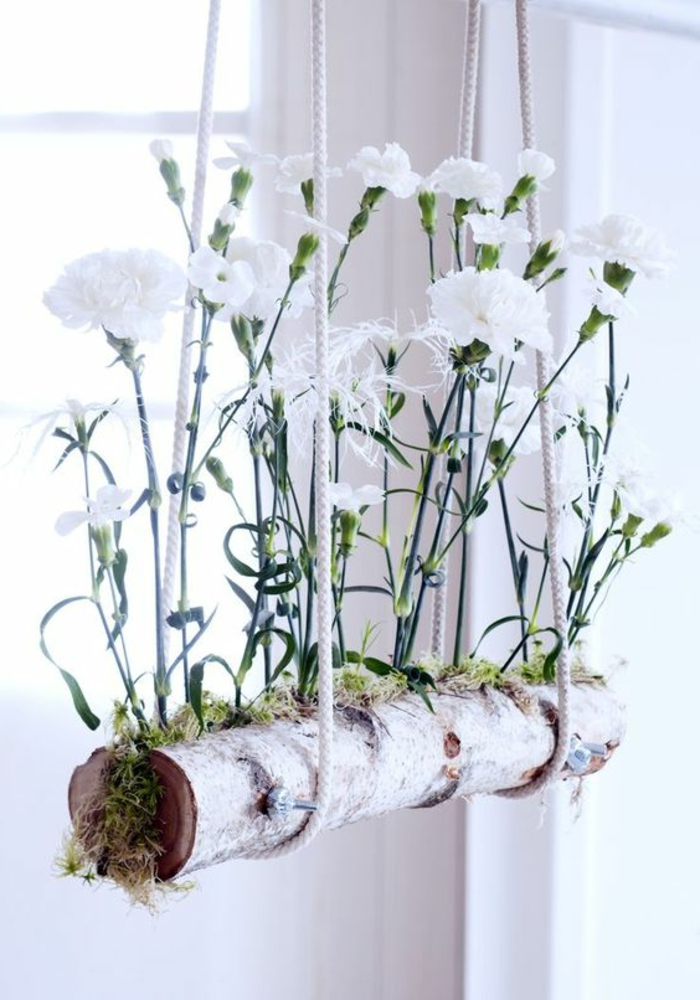 summer crafts, hanging planter made from white birch, containing green moss and white planted carnations