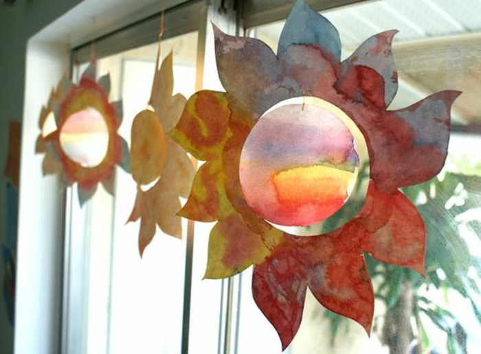 easy fun diys, several sun-shaped paper decorations, painted with different watercolors, hanging from a window