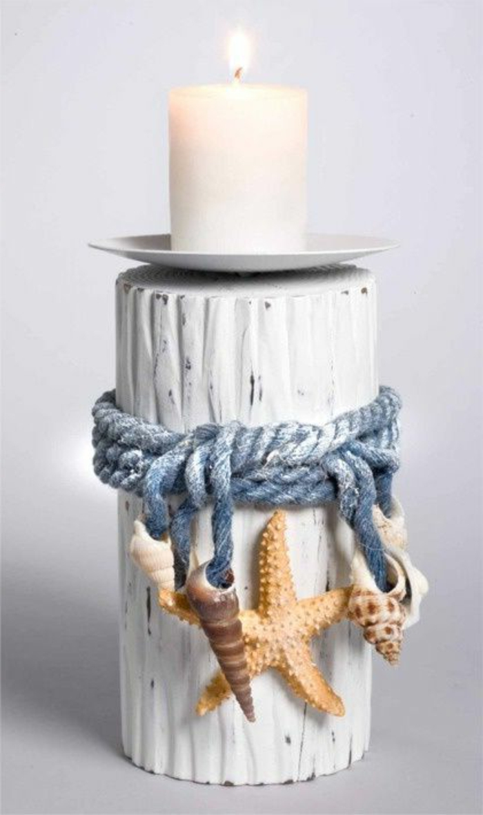summer crafts for adults, white lit candle, on a small white saucer, placed on a wooden holder, painted white and decorated with seashells and starfish, tied with a faded blue rope