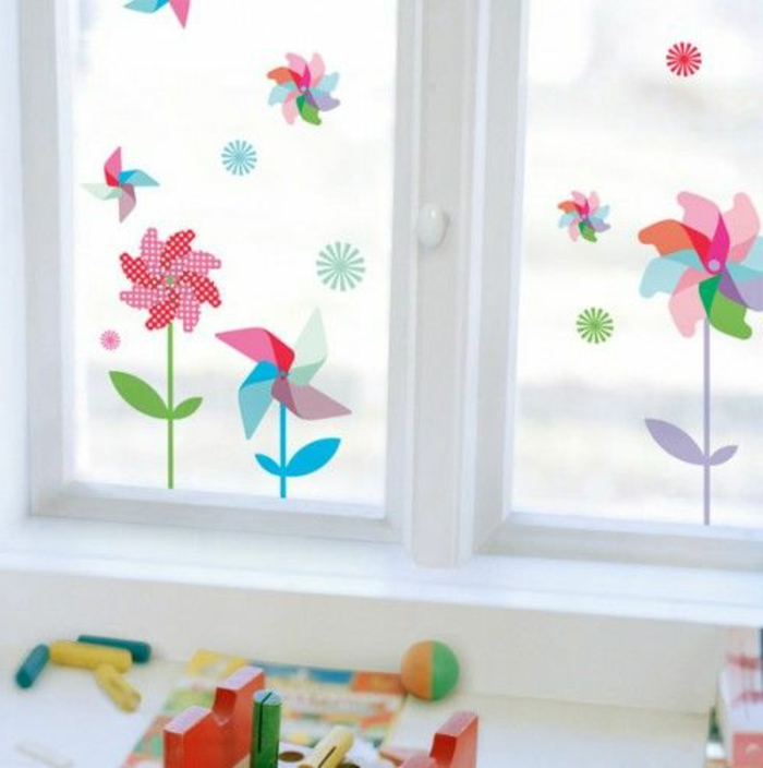 summer craft ideas, window with white panes, decorated with multicolored 2D flower stickers, shaped like wind spinners, colorful kid's toys strewn about
