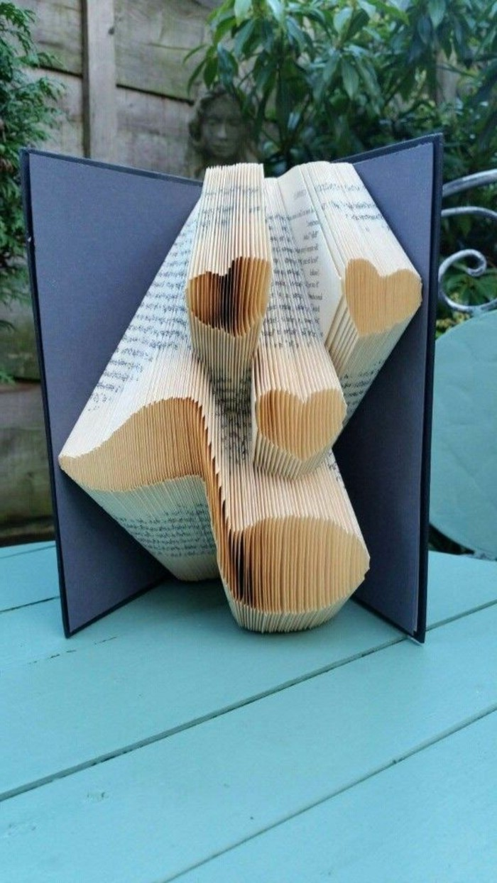 three hearts and a musical note, made from folded pages, inside an open book, with dark blue hard covers