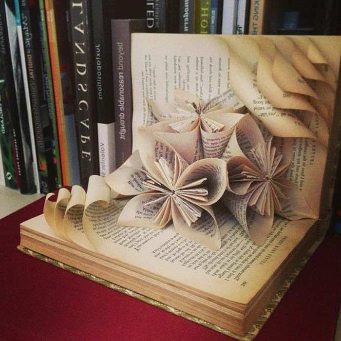 opened book, containing three flowers made from its pages, several other pages with rolled edges