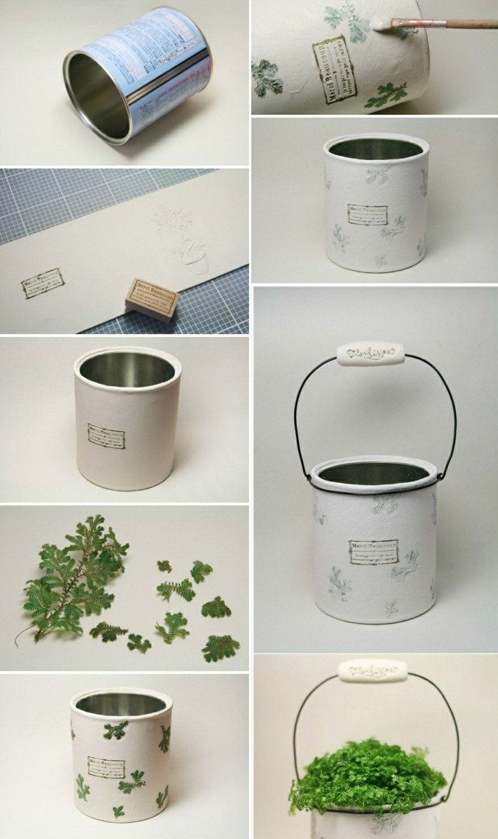 empty tin cans, flower pot made from a tin can, covered with white stamped paper, decorated with green leaves, containing green plant