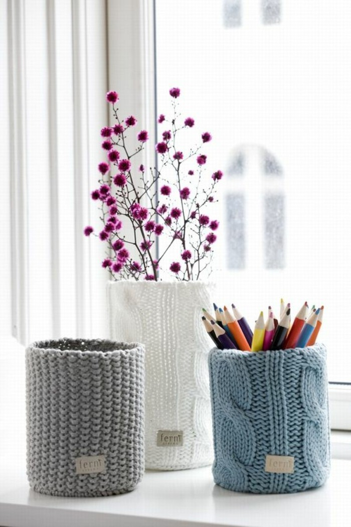 tin cans for crafts, three can knitted pencil holders in grey, white and light blue, containing colored pencils, and a dried purple plant