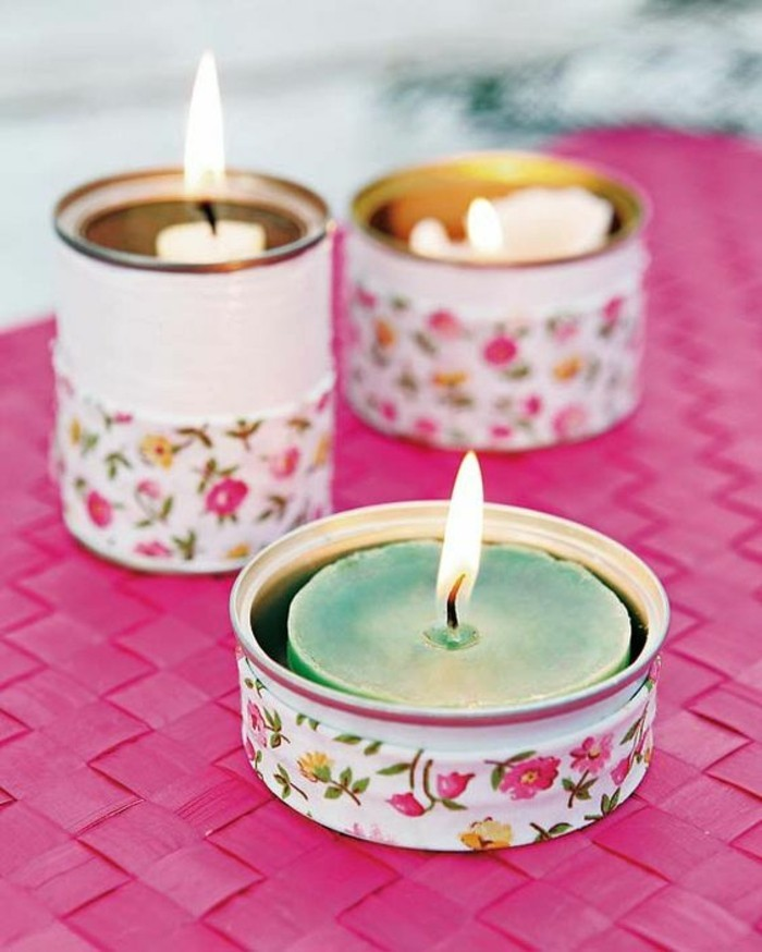 empty tin cans, three differently sized cans, painted white and decorated with floral paper, containing lit colors in different colors