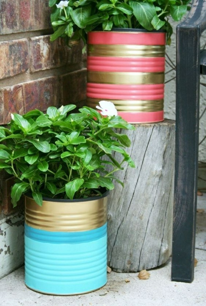 aluminum tins, two cans decorated with blue, pink and gold paint, containing green potted plants
