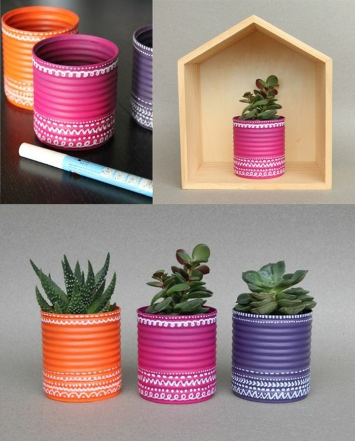 empty tin cans, three cans painted in orange, pink and violet, decorated with white marker, containing different succulents, pink can placed in wooden box