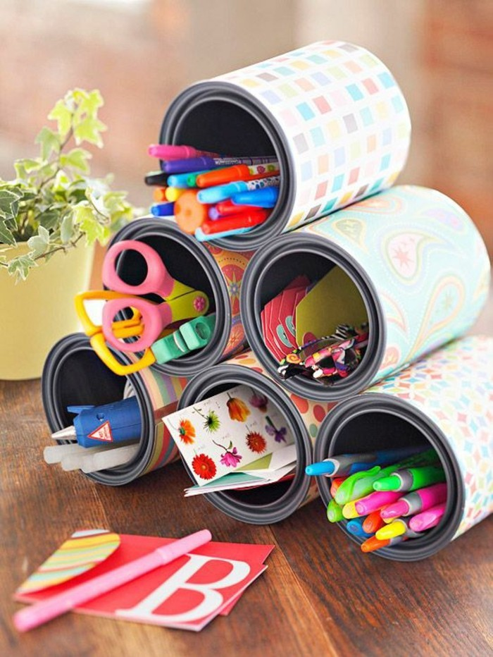 tin cans, six cans stacked in pyramid shape, decorated with multicolored patterned paper, containing pens and pencils, stickers and various stationary