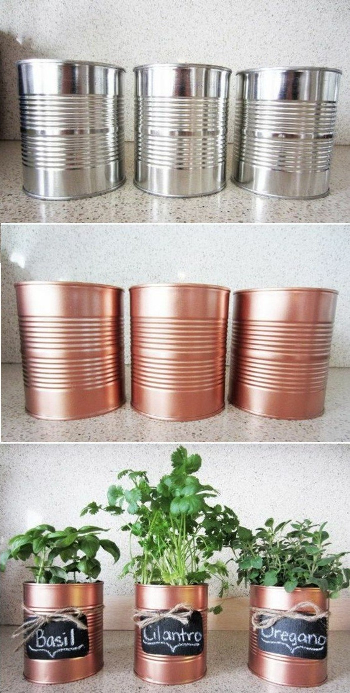 tin can crafts, three aluminium cans, colored with copper paint, with black labels tied with string, containing different planted green herbs