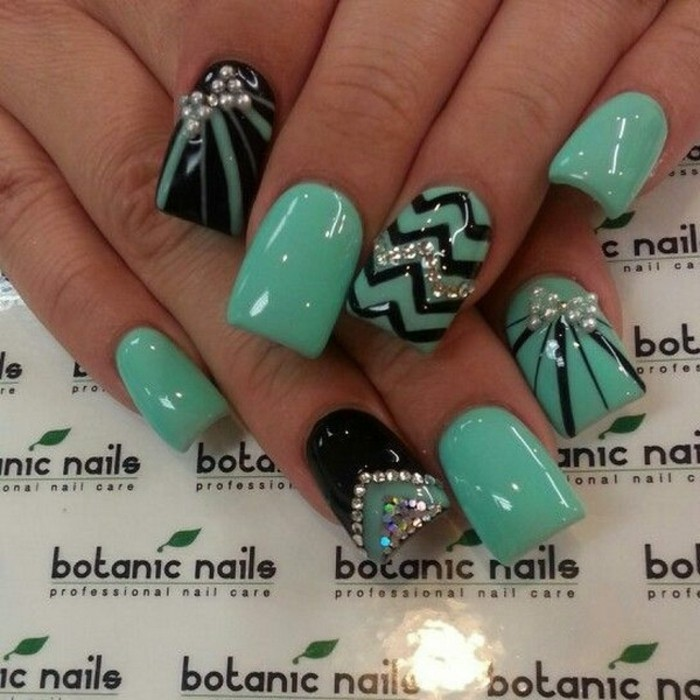eight fingernails painted in turquoise green, with black details and rhinestone decorations
