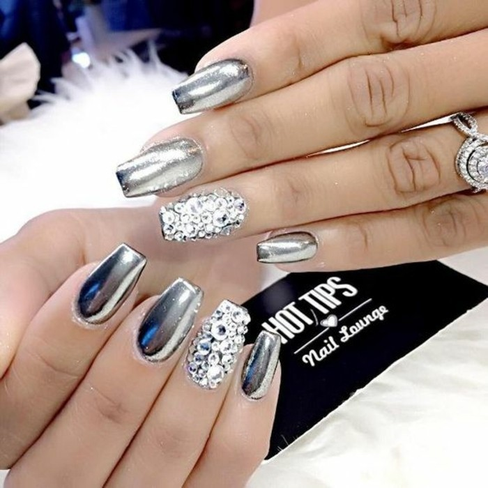 eight nails painted in shiny, metallic silver polish, ring fingers' nails covered in silver rhinestones