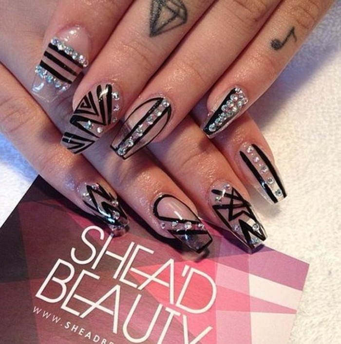 close up of two hands with finger tattoos, decorated with clear fake nails, with rhinestones and black details