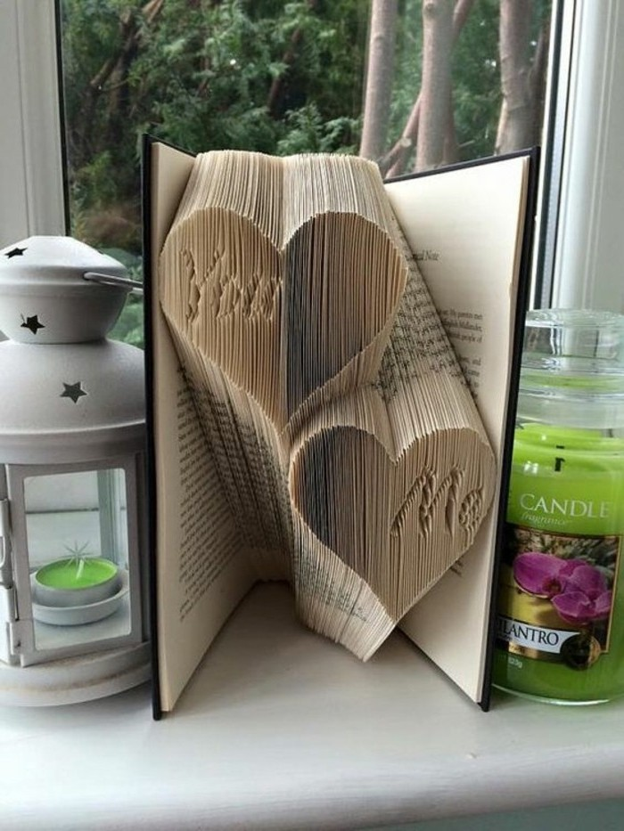 two heart shapes, with the inscription you and me, made from folded pages, inside a vintage book, with black hard covers