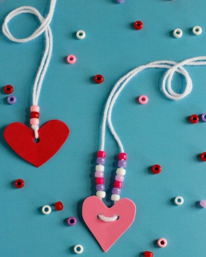 two heart-shaped felt cutouts in pink and red, attached to necklaces made of white string, decorated with pink, white and violet beads