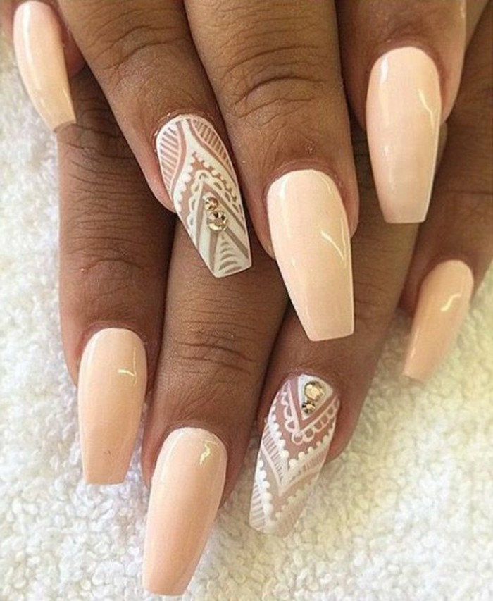 tan hands with pale peach-colored nail polish, ring fingers' decorated with rhinestones, and painted over with white figures