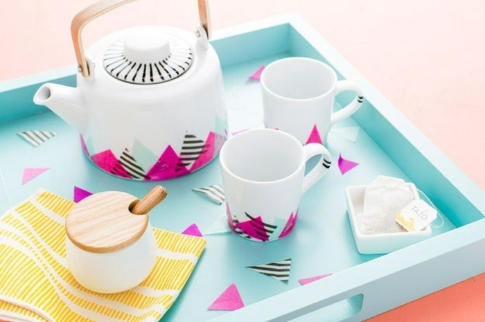best friend gift ideas, white tea pot and two mugs, decorated with triangular bits of colorful paper, on pale blue tray