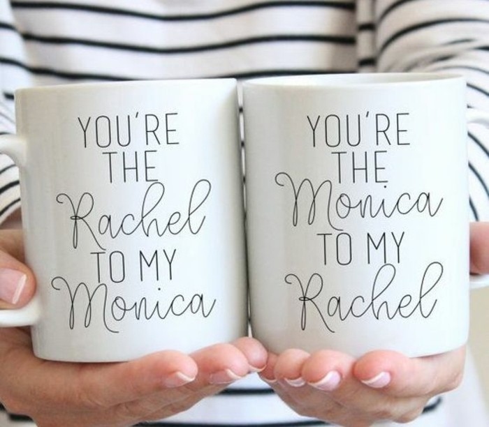 what to get your best friend for her birthday, close up of female hands, holding two white mugs with black writing