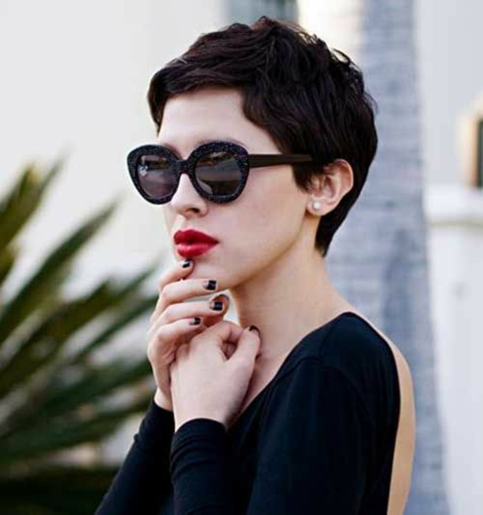 woman with very short dark wavy hair, wearing black retro sunglasses, bright red lipstick, and black open back top