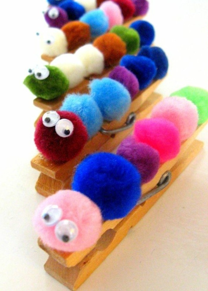 several wooden clothes pegs, with pom poms in different colors, decorated with googly stick-on eyes, looking like caterpillars
