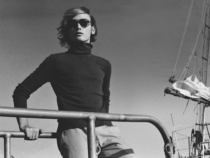 mid length hair, young man with sunglasses, wavy side-parted hair, black turtleneck and lightly colored trousers