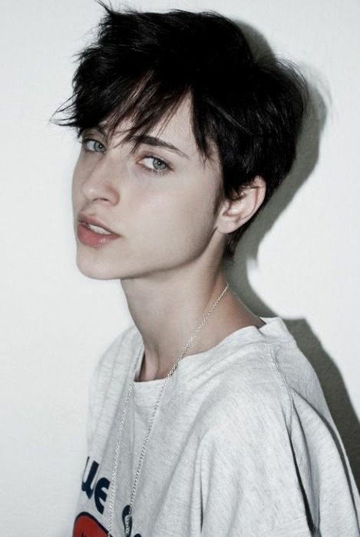 cute short haircuts, young woman with dark masculine haircut, messy bangs falling on her face, wearing pale grey t-shirt and silver chain