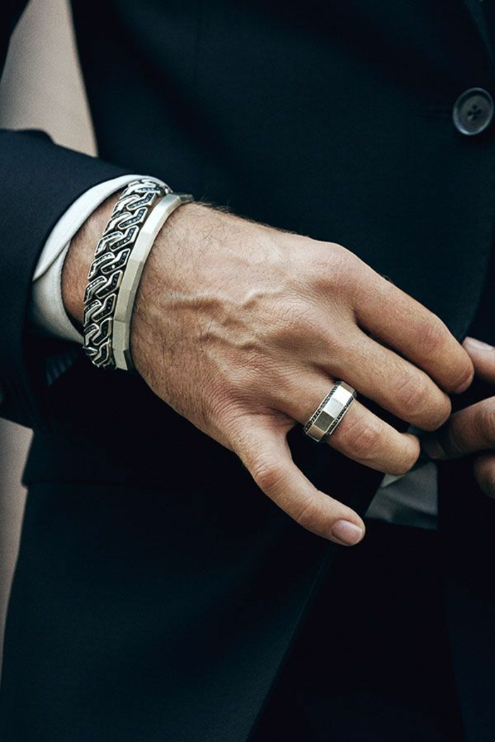 platinum or silver jewelery, consisting of a woven encrusted ornamental bracelet, and a minimalist bracelet, with matching ring, business casual attire, worn by man in dark suit