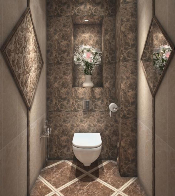 bathroom decor ideas, toilet with light and dark brown tiles on floor and walls, plain white toilet seat, mirror on one wall, bouquet of flowers on other wall