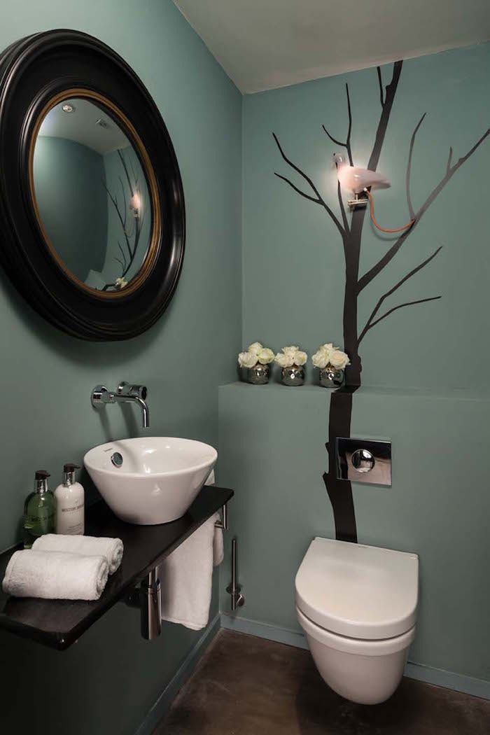 bathroom decorating ideas, toilet with walls in duck egg's blue, one wall is decorated by a mural of black leafless tree, round mirror with large dark wooden frame hangs on other visible wall
