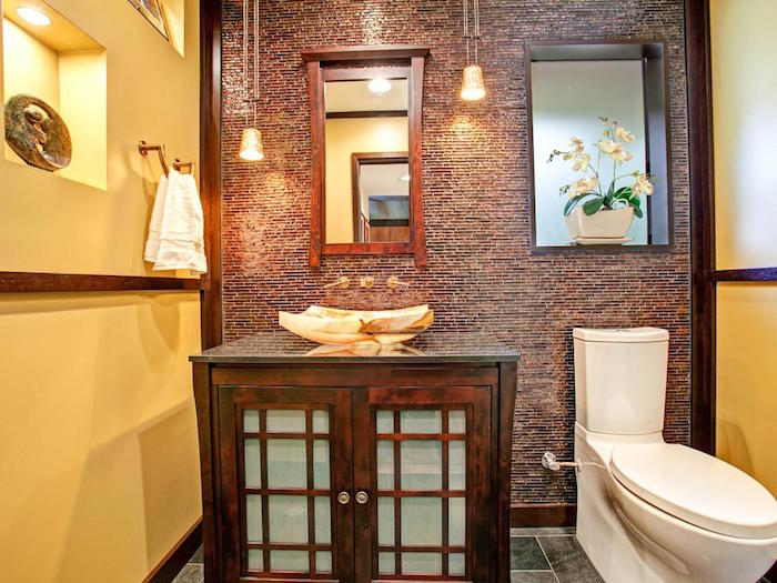 bathroom decorating ideas, toilet with two yellow walls, and a third wall decorated with brown mosaic, wooden beams and trims, large wooden cupboard with unusual sink, modern white toilet