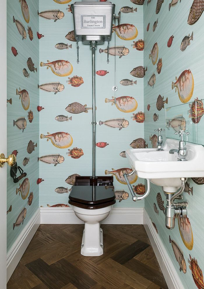 small bathroom ideas, narrow toilet with pale blue, fish patterned wallpaper, antique toilet seat and sink, dark wooden floors