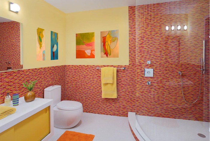 bathroom ideas, large room with big glass shower cabin, white and yellow slide cupboard, round modern white toilet seat, walls half covered with red, orange and yellow mosaic, other half painted in yellow, large mirror and paintings on walls