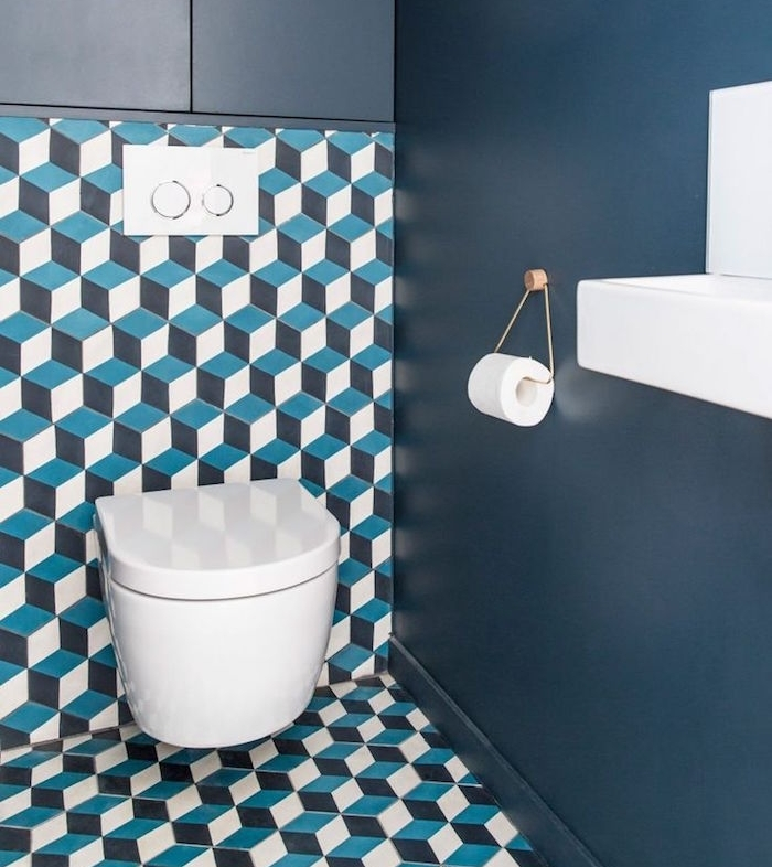 bathroom remodel, toilet with dark blue wall, other visible wall and floor have an unusual covering with geometric, faux 3D patterns in white, dark and light blue, modern white toilet seat and sink