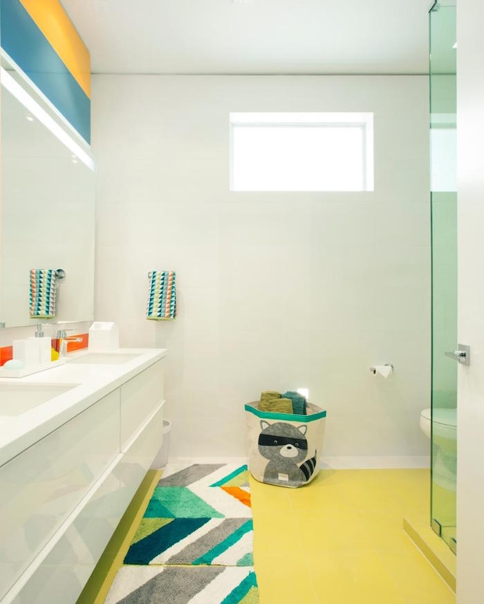 bathroom remodeling, spacious bathroom with large, white double sink, pastel yellow floor, four multicolored rugs, large mirror and blue and yellow stripes on wall above