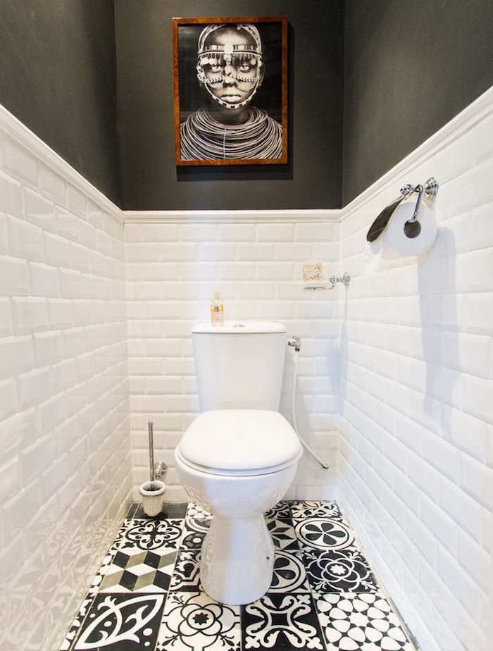 bathroom remodels, narrow toilet with black and white, patterned and mismatched tiles on floor, lower half of the walls are covered in white bricks, upper part of the walls are painted black, classic white toilet seat, black and white portrait in wooden frame