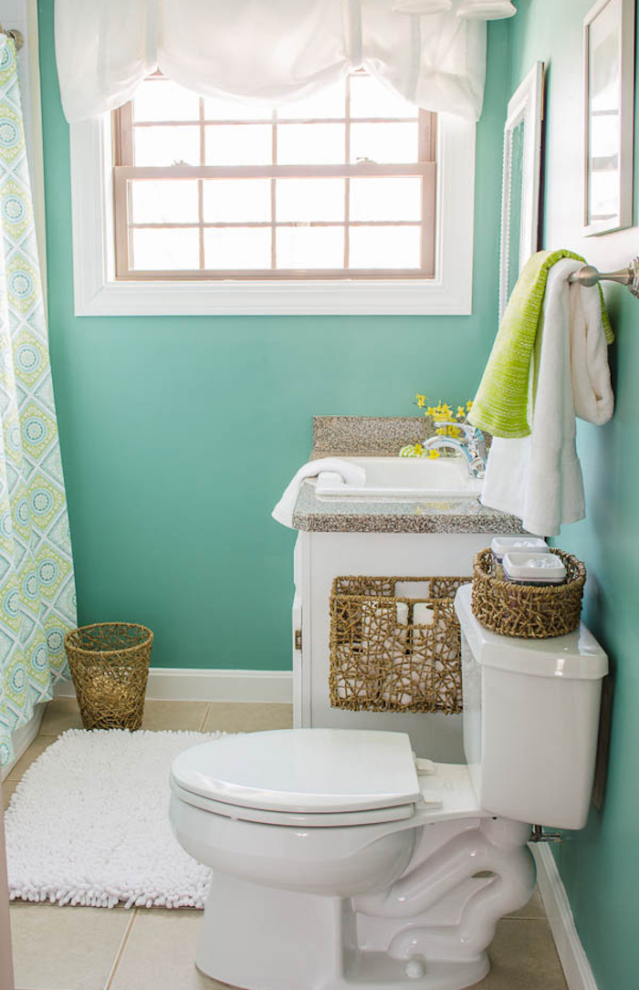 bathroom ideas, toilet with pastel turquoise walls, light cream tiled floor, classic toilet seat, white and faux marble sink, fluffy white rug and whicker details