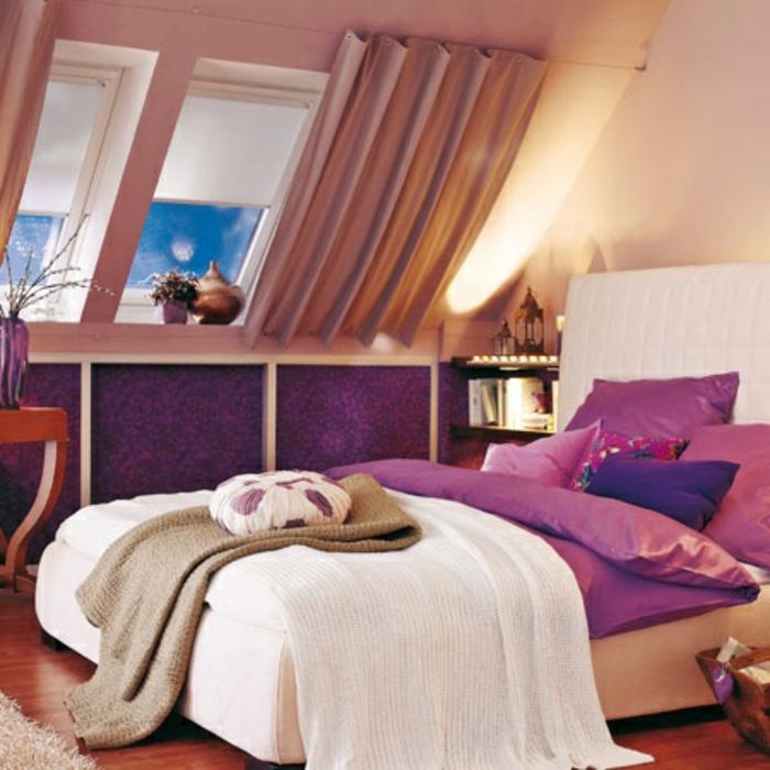 curtains ideas, room with purple paneling, bed in white and purple, with many cushions, sloped window with light brown, gathered curtains and pale window covers
