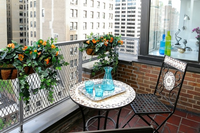round metal table with mosaic-effect top, with tray containing blue glasses and jug, near matching chair, orange potted flowers