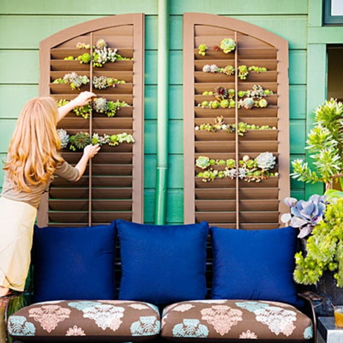blonde woman decorating wooden window blinds, with small succulents, brown couch with pale blue and pink pattern, and blue pillows nearby, front porch décor with plants