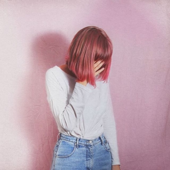 woman with pink pageboy haircut with bangs, wearing a pale grey sweater, and high-waisted retro jeans, hiding her face with one hand