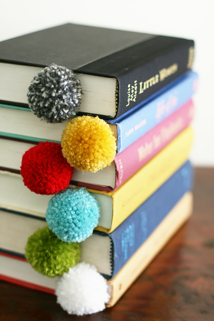 a stack of six books, with differently colored hard covers, containing dividers, decorated with differently colored pom-poms, diy craft projects
