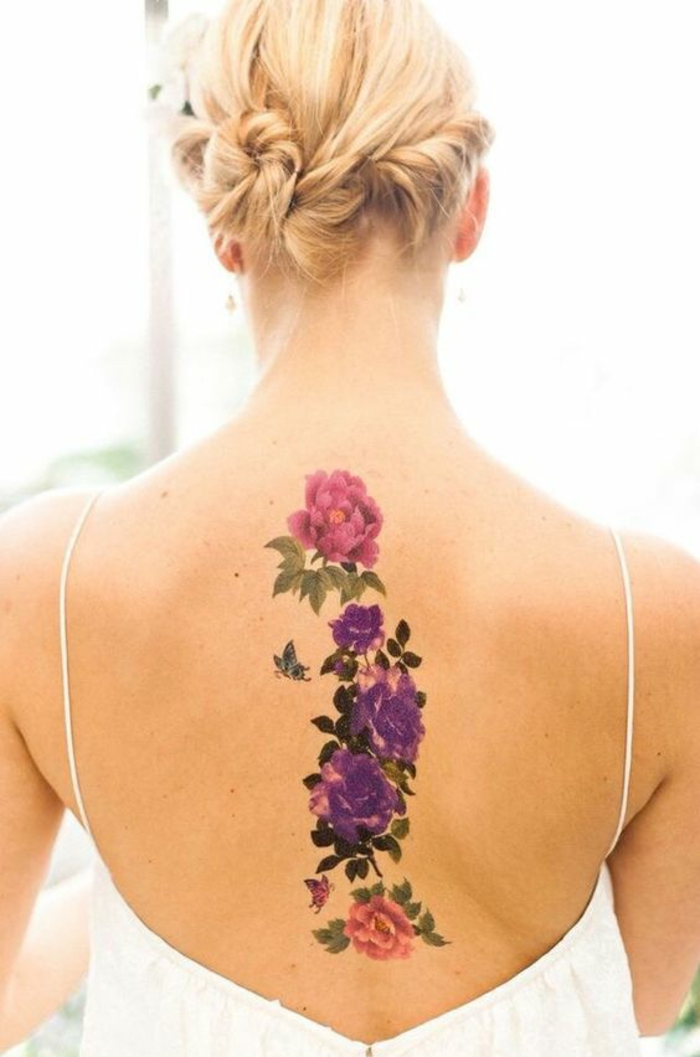 traditional flower tattoo, blond woman with hair put up, wearing a white open back top, revealing a large, vertical tattoo of a pink peony, above several violet roses, and a single pink rose, many dark and light green leaves