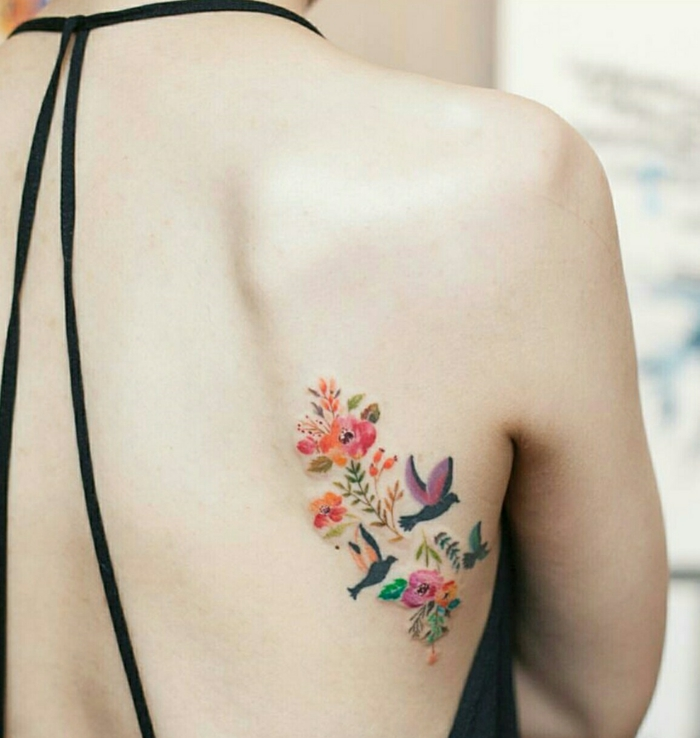 shoulder flower tattoos, woman with open back top, with thin black straps, a multicolored tattoo of several stylized poppies and other plants, with three birds in flight, done on her back, under her shoulder