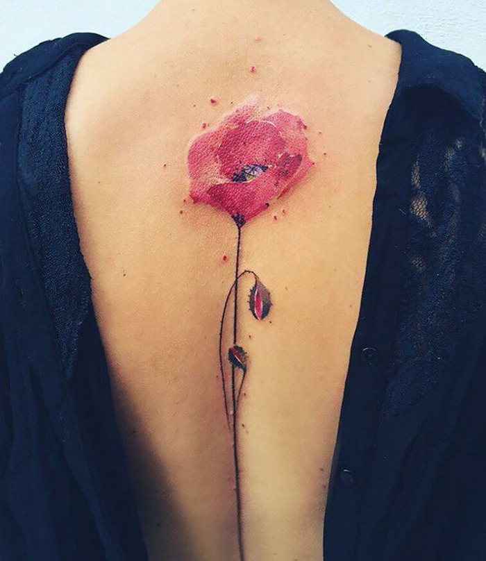 close up of a woman's back, with a water-color effect tattoo of a red poppy, with a thin green stalk and two buds