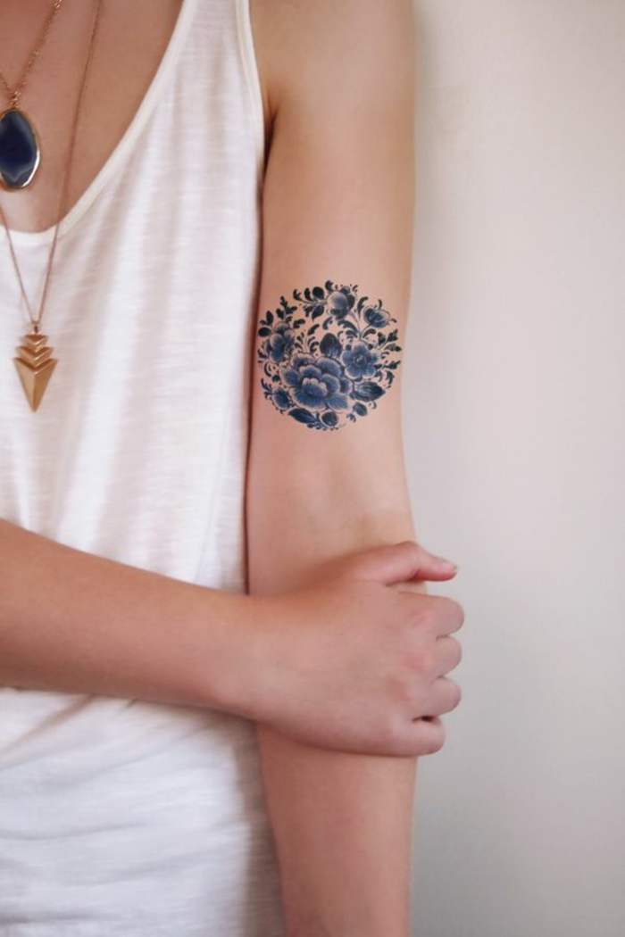 traditional flower tattoo, round blue tattoo, made up of many, differently sized and shaped blossoms and leaves, on a woman's upper arm