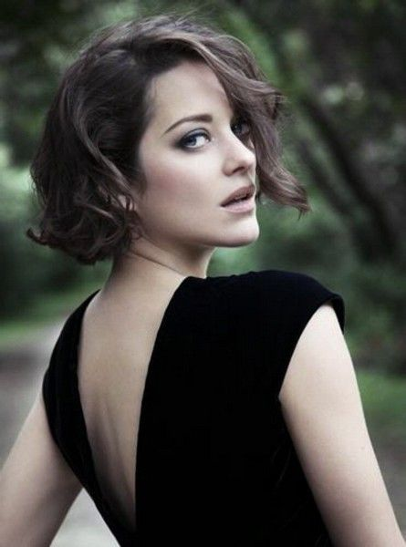 marion cotillard, in black open back dress, looking over her shoulder, with curly side-parted brunette hair, short bob hairstyles