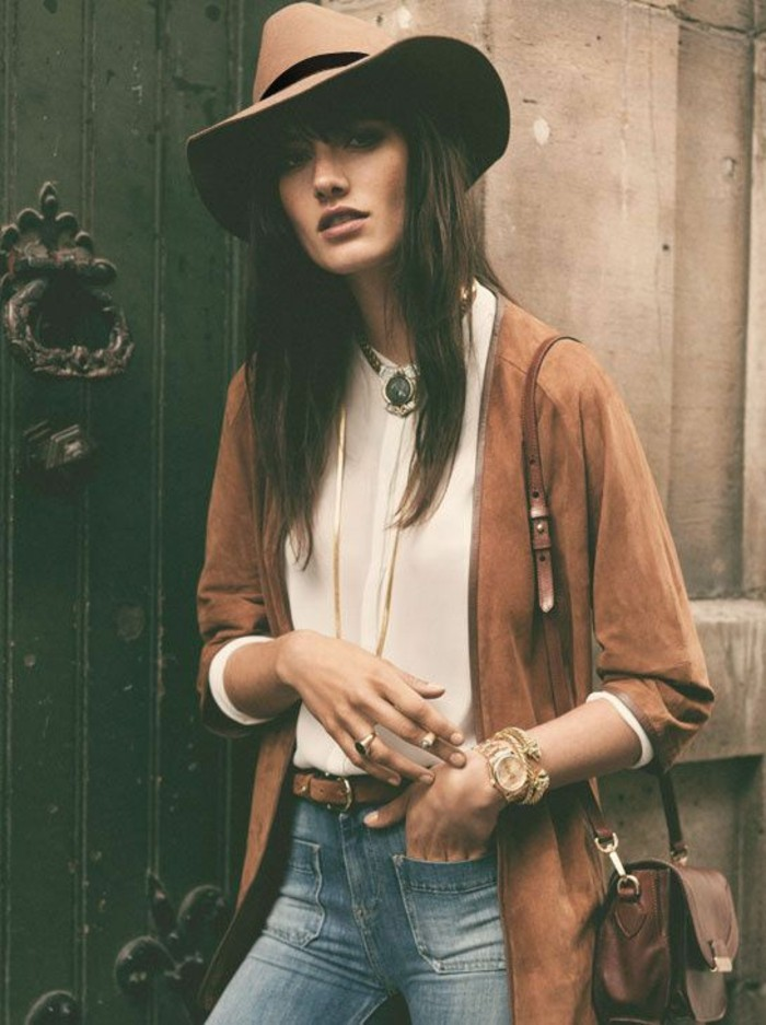 casual business attire, camel colored suede cardigan, worn over pale cream shirt, and jeans with front pockets and belt, by brunette woman in pale beige felt hat