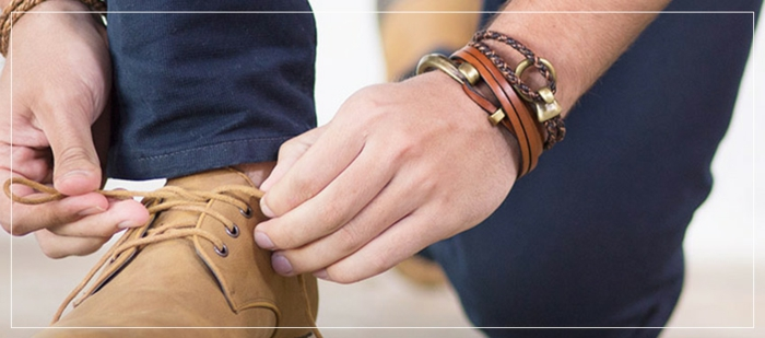 close up of man's hands, decorated with bracelets, made of leather and metal, tying his shoelaces, business casual shoes in cream