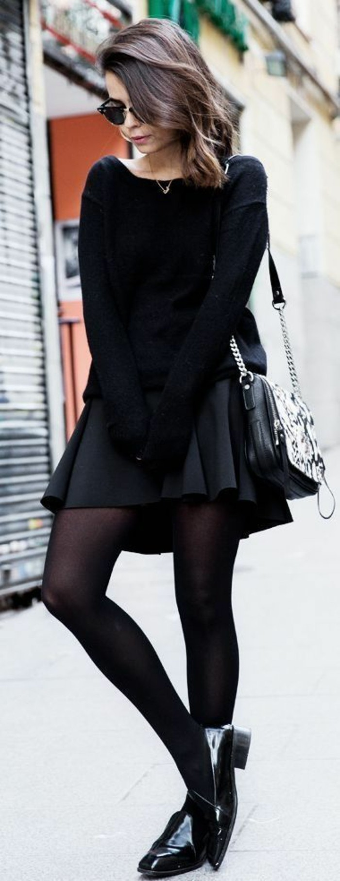 casual business attire, brunette woman with sunglasses, wearing an all-black outfit, with skirt and sweater, tights and flat patent leather shoes