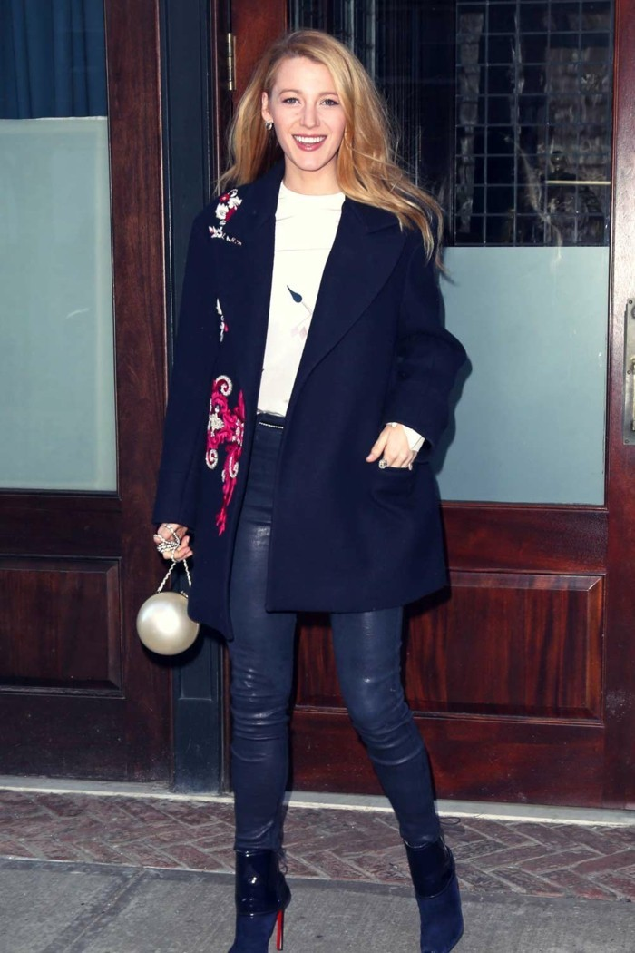 business casual women, blake lively with long blonde hair, wearing shiny black skinny trousers, white top and a large, dark coat with red and white embroidery