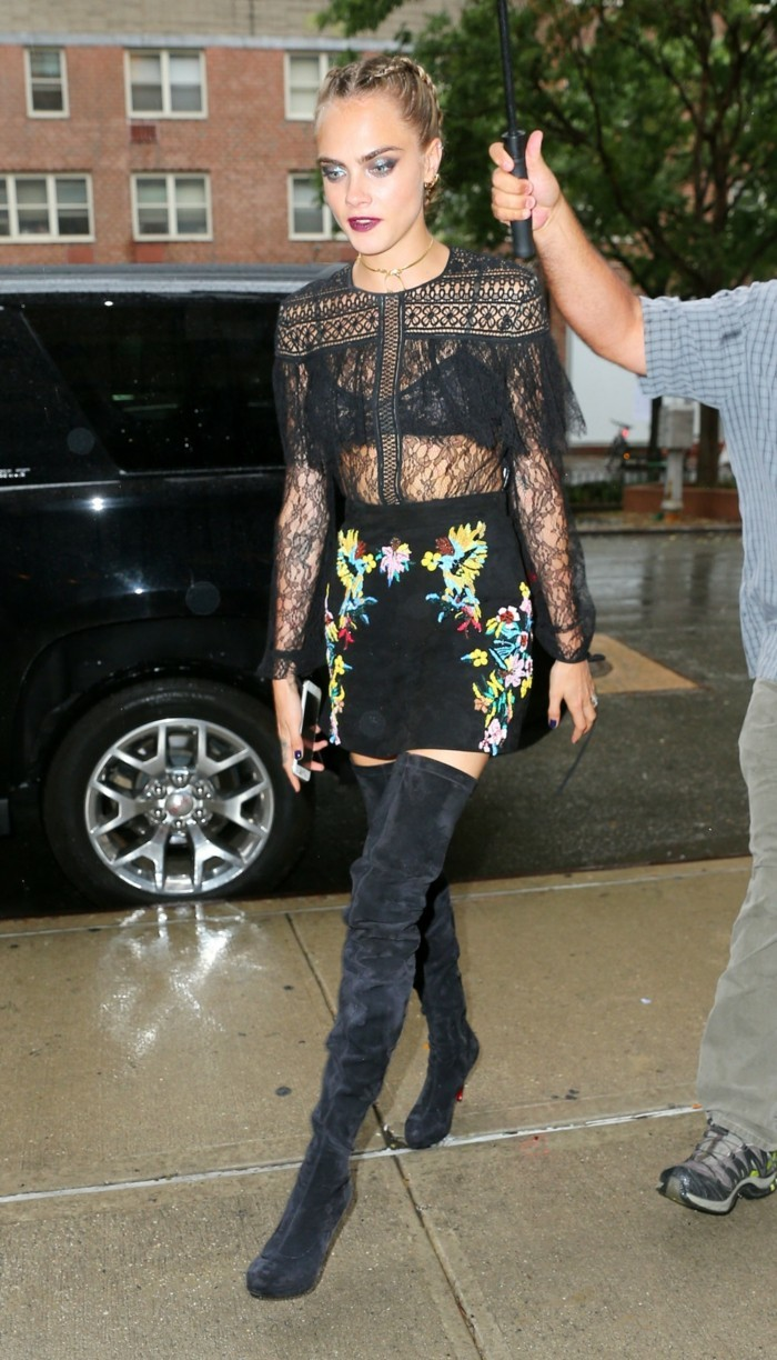 cara delevigne with tied hair and heavy make-up, wearing sheer black lace shirt, with black bra, black suede skirt with floral embroidery, and black velvet over the knee boots